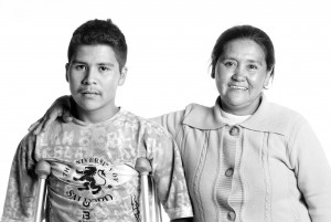 A photo depicting the direct and indirect impact of landmine contamination on a mother and son in Colombia - disabled son and caregiving mother.
